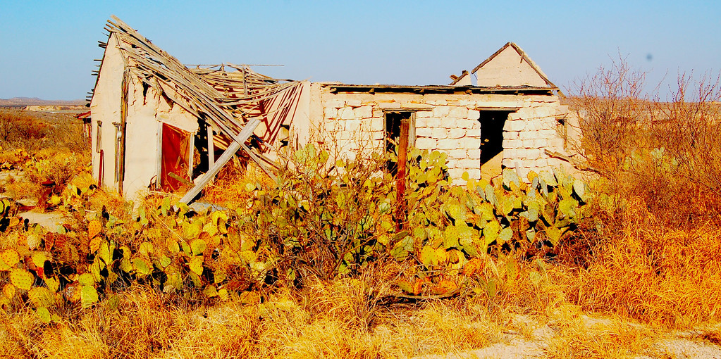 """""""Many buildings in Langtry are abandoned. Some roads are unpaved and the whole place has a rather faded air. One dirt road winds down to an open place suitable for camping in the Rio Grande river valley, which has quite impressive sandstone cliffs on the Mexican side."""""""